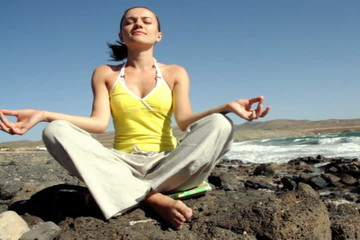 Young woman meditating by the sea