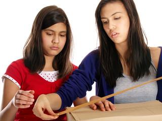 teenage girls packing a cardboard box