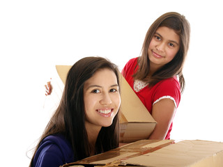 smiling girls carrying cardboard boxes