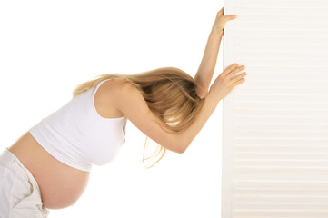 tired pregnant woman leaned on the door
