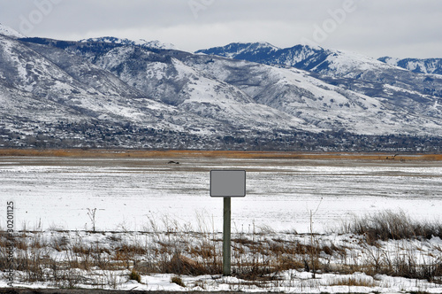 Blank Sign in Broad Field in Front of Mountain