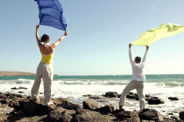 Couple with waving sarong standing on the seashore, slow motion