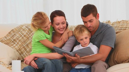 Family reading a children book on their couch