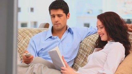 Man watching tv while his girlfriend is reading a book