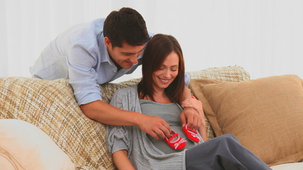 Couple playing with baby shoes on the sofa