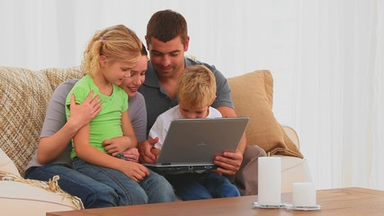 Familly looking at their laptop on the sofa