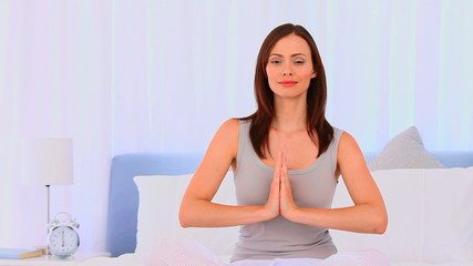 Peaceful woman practicing yoga on her bed