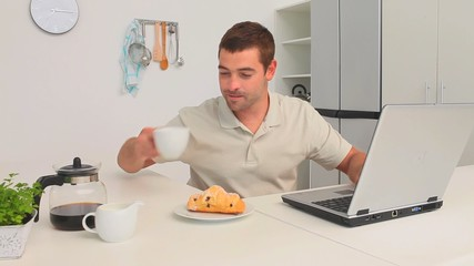 Man drinking a cup of coffee while he is working on his laptop