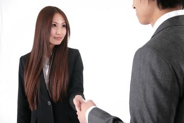 握手するスーツの男性と女性