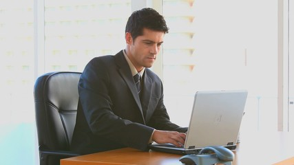 Businessman working on his laptop at work