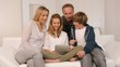 Family relaxing in sofa with electronic tablet
