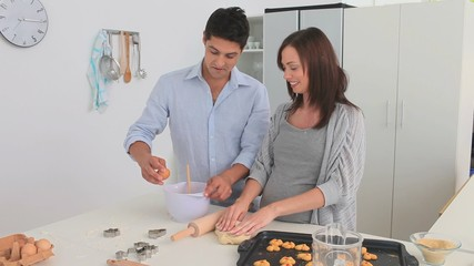 Pregnant woman baking with her husband