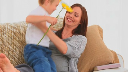 Boy offering a flower to his pregnant mother