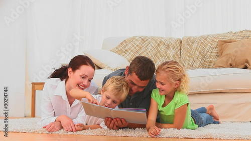 Family reading a book together on the floor