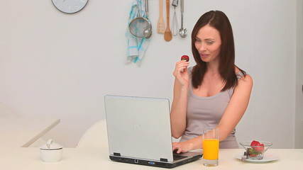 Woman eating strawberry in front of her laptop
