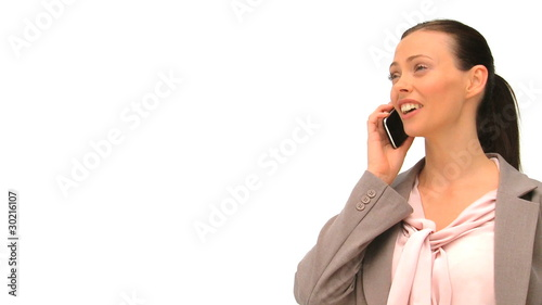 Radiant woman phoning against a white background