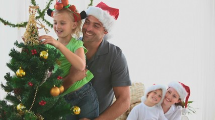 Family decorating a Christmas tree
