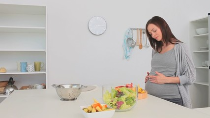 Pregnant woman preparing a salad