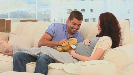Lovely couple playing with a teddy bear