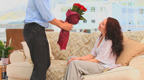 Man bringing a bunch of flowers to his wife