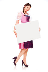 Beautiful young girl with dirndl dress holding white board