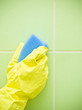 Hand in yellow protective glove cleaning wall