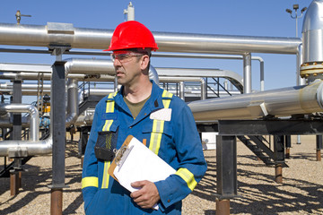 Male gas field operator inspects compressor site