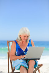 Woman working on her laptop on the beach