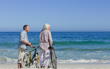 Senior couple with their bikes on the beach