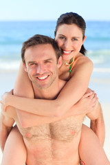 Man having wife a piggyback on the beach