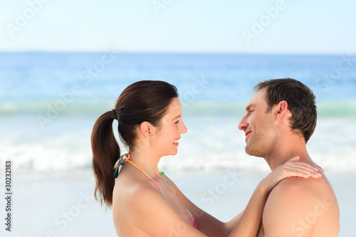 Adorable couple huging on the beach