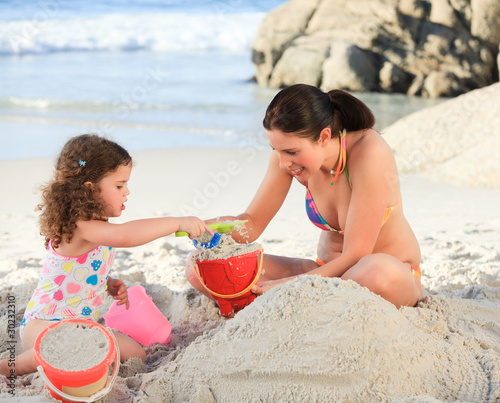Daughter with her mother making a sand castle