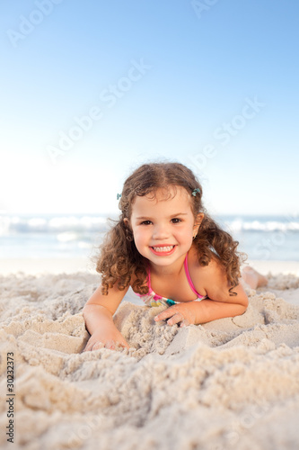 Little girl lying down on the beach