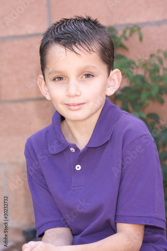 Portrait young biracial boy with short hair by brick wall
