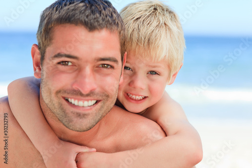 Smiling father having son a piggyback at the beach
