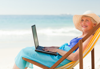 Happy woman working on her laptop at the beach