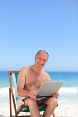 Retired man working on his laptop on the beach