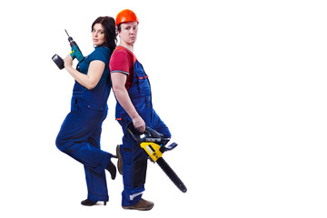 Man and woman with the chainsaw and drill are standing back to b