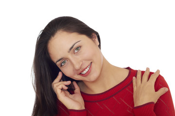 Young beautiful woman in red sweater talks on cellular telephone