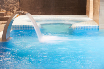 Empty Spa pool with waterfall jet and jacuzzy in action