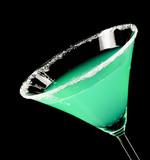 Martini glass with green coctail on black background