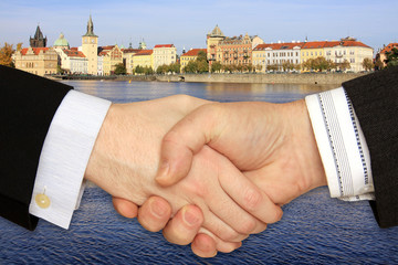 Businessmen shaking hands in front of historical Buildings