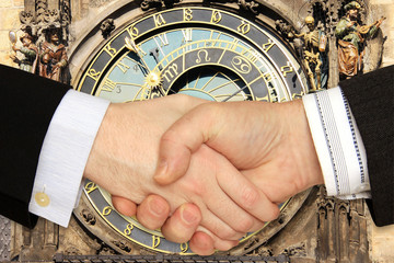 Businessmen shaking hands in front of the historical Clock