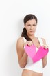 Lovelorn female pulling a paper heart to pieces