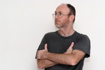 Unshaved disheveled man in spectacles frowning sullenly