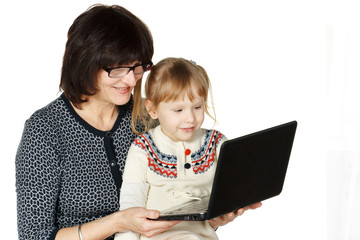 Grandmother demonstrating her granddaughter smth in laptop