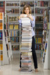 Young woman standing with big stack of books