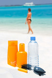 Sunglasses, water and sun protection cream on beach background poster