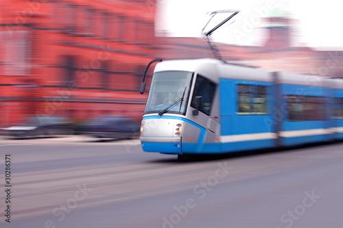 Modern  blue tram rider fast on rails - 30286371