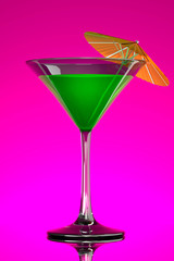 green tropical martini cocktail with orange umbrella